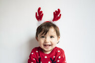 Portrait of laughing baby girl wearing reindeer antlers headband - GEMF01941