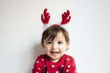 Portrait of laughing baby girl wearing reindeer antlers headband - GEMF01941