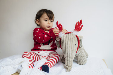 Baby girl playing with reindeer antlers headband and toy elephant - GEMF01944