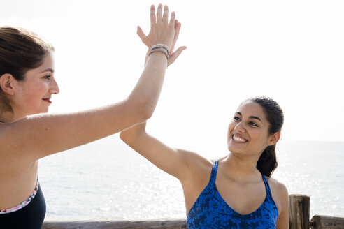 Two young women training together on sea waterfront, high fiving - CUF02043