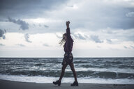 Young woman walking on beach with arms raised at dusk, Odessa Oblast, Ukraine - CUF02055