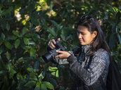 Woman taking pictures with mirrorless digital camera,  Shinjuku Gyoen National Garden, Tokyo - CUF02079