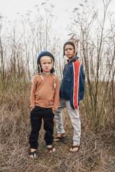 Portrait of two brothers, outdoors, wearing knitted hats, making faces - CUF02097