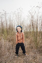 Portrait of boy in rural setting, hands in pockets, smiling - CUF02103
