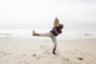 Young boy standing on beach,balancing on one leg - CUF02106