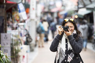 Woman taking pictures with mirrorless digital camera in street, Tokyo - CUF02127