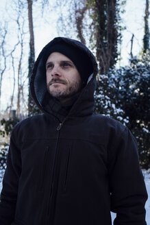 Man keeping warm in hooded jacket in winter weather - CUF02142