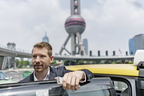 Young businessman getting out of yellow cab at Shanghai financial centre, Shanghai, China - CUF02184