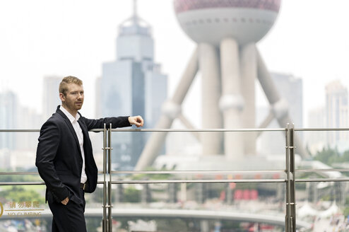 Young businessman leaning on handrail at Shanghai financial centre, Shanghai, China - CUF02187