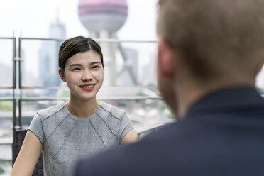 Over shoulder view of young businesswoman and man having meeting at sidewalk cafe in Shanghai financial centre, Shanghai, China - CUF02190