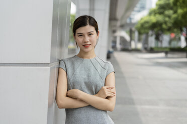 Portrait of young businesswoman leaning against wall in city, Shanghai, China - CUF02196
