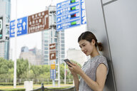 Young businesswoman looking at smartphone in city, Shanghai, China - CUF02199