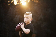 Portrait of confident boy practicing american football, holding ball in garden - CUF02205