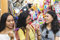 Happy young women with ice lollies in bazaar, Bangkok, Thailand - CUF02214