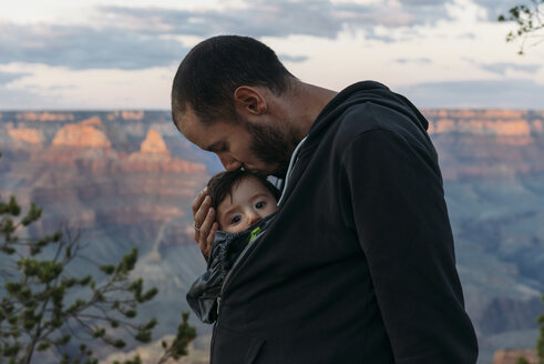 USA, Arizona, Grand Canyon National Park, father kissing baby girl at sunset - GEMF01947