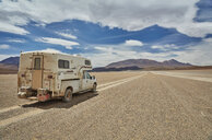 Recreational vehicle, travelling across landscape, rear view, Villa Alota, Potosi, Bolivia, South America - CUF02306