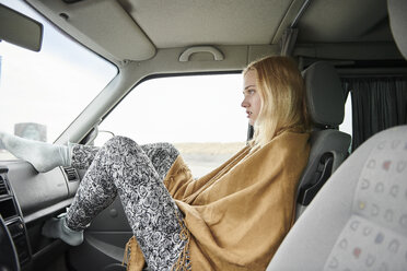 Blond young woman sitting in car looking at distance - MMIF00002