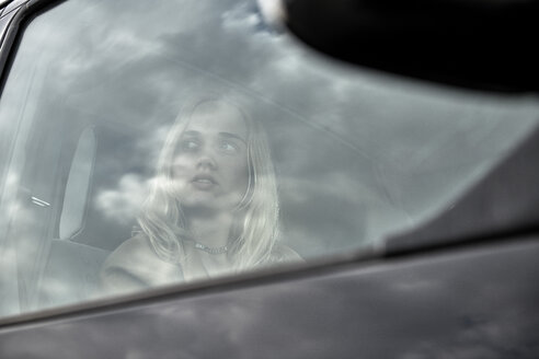 Young woman sitting in a car looking out of window - MMIF00005