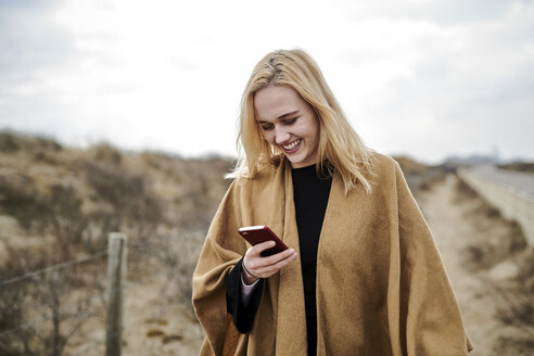 Laughing young woman looking at smartphone on the beach - MMIF00011