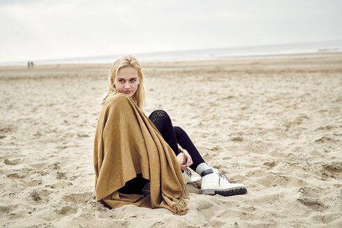 Netherlands, portrait of blond young woman sitting on the beach - MMIF00014