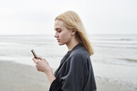 Netherlands, blond young woman using smartphone on the beach - MMIF00023