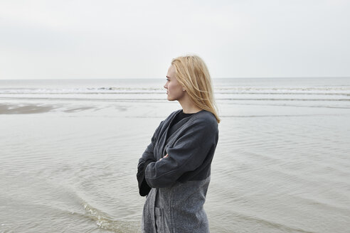 Netherlands, blond young woman standing on the beach looking at distance - MMIF00026
