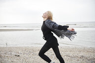 Netherlands, happy blond young woman running on the beach - MMIF00029