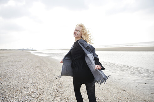 Netherlands, portrait of blond young woman running on the beach - MMIF00032