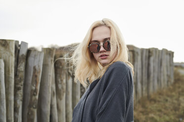 Portrait of blond young woman wearing mirrored sunglasses on the beach - MMIF00038