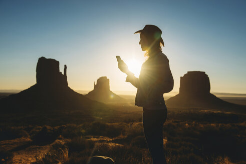 USA, Utah, Woman using mobile at sunrise in Monument Valley - GEMF01953