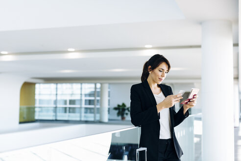 Businesswoman using mobile phone for electronic check-in - CUF02419