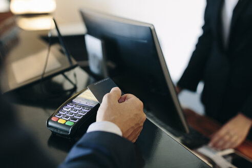 Businessman making contactless payment at hotel reception - CUF02434