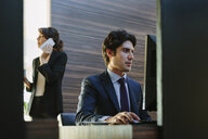 Businessman and businesswoman working in business centre in hotel - CUF02449
