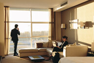 Businessman and businesswoman working in hotel bedroom - CUF02455