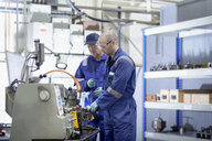 Engineers working at lathe in turbine maintenance factory - CUF02485