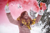 Young woman with smoke flare in snow - CUF02536