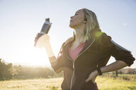Young woman exercising outdoors, holding water bottle - CUF02569