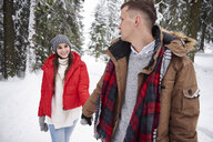 Young couple walking in snow - CUF02575