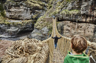 Over shoulder view of boy, brother and mother crossing Inca rope bridge, Huinchiri, Cusco, Peru - CUF02590