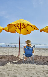 Rear view of female tourist sitting under beach umbrella, Camana, Arequipa, Peru - CUF02599