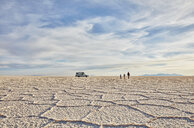 Mother and sons walking across salt flats, recreational vehicle in background, Salar de Uyuni, Uyuni, Oruro, Bolivia, South America - CUF02611