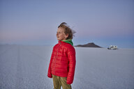 Young boy standing on salt flats, looking at view, recreational vehicle in background, Salar de Uyuni, Uyuni, Oruro, Bolivia, South America - CUF02614