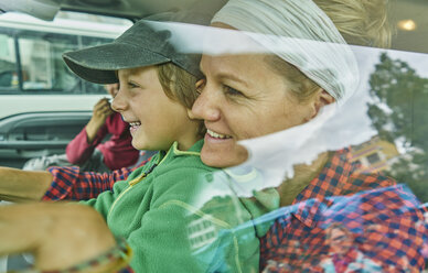Mother and sons inside vehicle, smiling, view through window - CUF02617