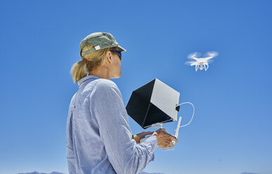 Woman flying drone, low angle view, Uyuni, Oruro, Bolivia, South America - CUF02620