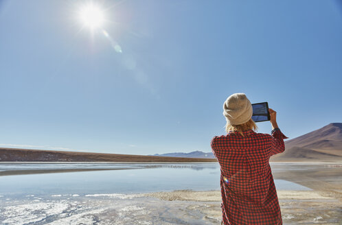 Woman photographing landscape, using digital tablet, Salar de Chalviri, Chalviri, Oruro, Bolivia, South America - CUF02626