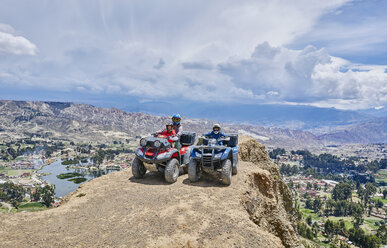 Mother and sons on top of mountain, using quad bikes, La Paz, Bolivia, South America - CUF02635