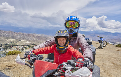 Mother and son on top of mountain, using quad bike, La Paz, Bolivia, South America - CUF02638