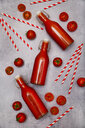 Homemade tomato juice in swing top bottles, straws and tomatoes on grey ground - RTBF01266