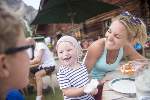 Happy little girl eating cake with family at alpine hut - HHF05561