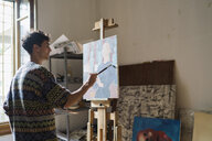 Male artist painting canvas at easel in artists studio - CUF02726